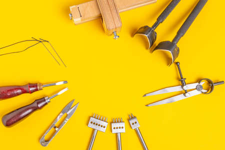 Leather craft tools on a yellow background. Handmade theme