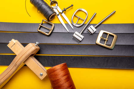 Sewing process of the leather belt. Tools, materials and accessories for leather workshop. Vintage sewing industrial Standard-Bild - 121046893