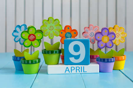 April 9th. Image of april 9 wooden color calendar on white background with flowers.  Spring day, empty space for text Standard-Bild - 121046897