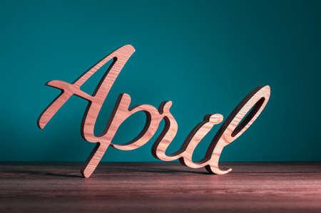 Hello April wooden texe written on dark background. Spring time concept Standard-Bild - 121046899