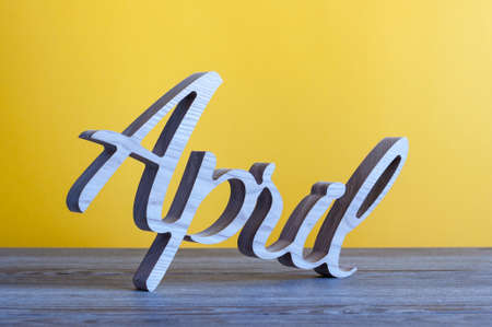 April month, calendar on table with yellow background. Spring time Standard-Bild - 121046900