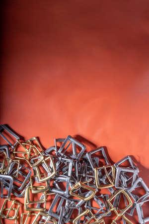 Belt buckles on red full grain leather background. Materials, accessories on leather craftmans work desk Standard-Bild - 121047236