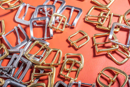 A lot of metal buckles for belts on red genuine full grain leather. Leather workshop Standard-Bild - 121047240