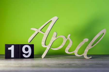 April 19th. Day 19 of month, calendar on wooden table and green background. Spring time, empty space for text Standard-Bild - 121047249