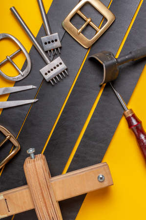 Handmade leather craft tools, belt buckle and black leather straps on yellow background
