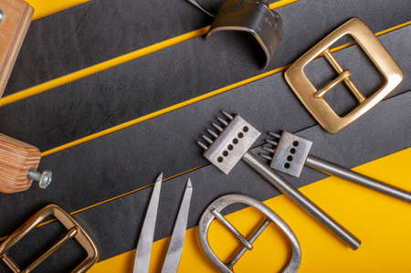 Handmade leather craft tools, belt buckle and black leather straps on yellow background Standard-Bild - 121046902