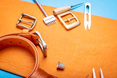 Belt buckles with leather tools on orange full grain leather background. Materials, accessories on craftmans work desk Standard-Bild - 121046909