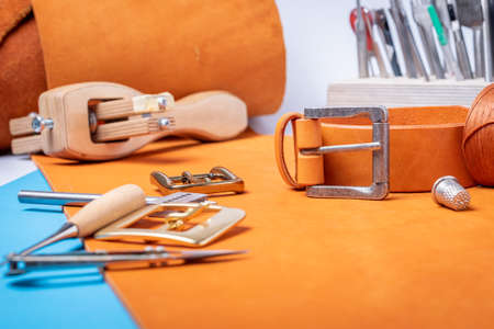 Belt buckles with leather tools on orange full grain leather background. Materials, accessories on craftmans work desk