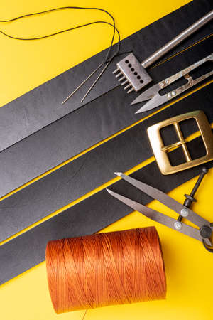 Sewing process of the leather belt. Tools, materials and accessories for leather workshop. Vintage sewing industrial. Standard-Bild - 121047227