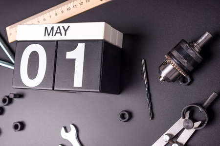 May 1st - Labour day. Day 1 of may month, calendar on black background with workers tools 写真素材