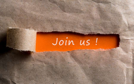 Join us - message appearing behind torn brown paper. Hiring and new job concept 写真素材