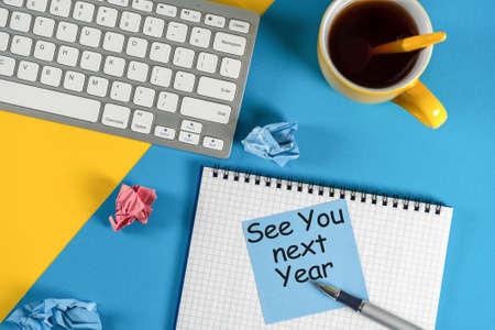 Mensaje empresarial Nos vemos el próximo año escrito en un portátil, con teclado, suministros de oficina en la mesa azul en segundo plano. Foto de archivo