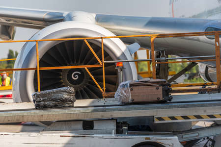 Travel bags and airplane in airport. Loading suitcases on an aircraft, preparing for flight Stockfoto