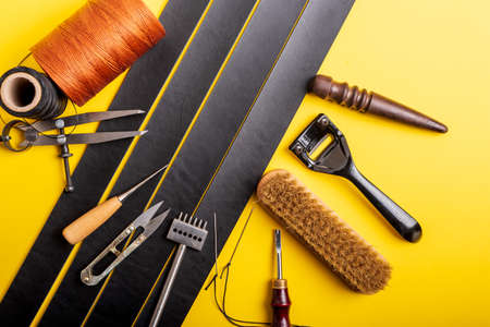 Leather working or Leather craft. Black tanned leather on leather craftmans work desk . Working tools on a work table
