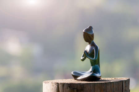 Figure of beautiful young girl meditating and do yoga on wooden surface. With empty space for text.