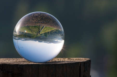 Glass ball on a hemp on a background of green mountains