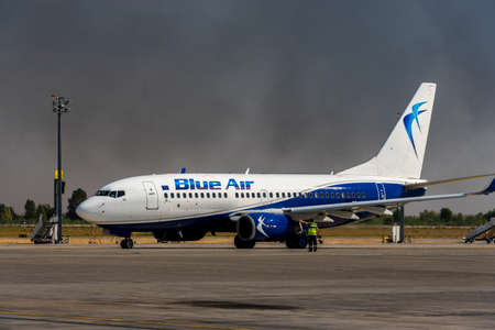KYIV, UKRAINE - SEPTEMBER 10, 2019: Blue Air Airlines. Airplane is preparing to fly on a background of black smoke