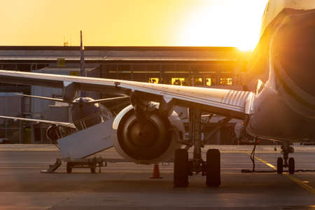 Large passenger airliner in the sunset against the background of the airport terminal. Travel by aircraft.
