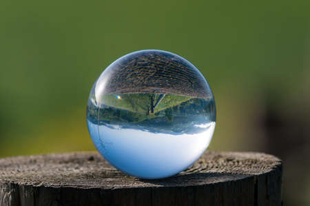 Glass ball on a hemp on a background of green mountains.