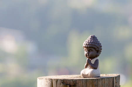 silhouette of little buddha or baby practicing yoga, meditate and pray on wooden surface