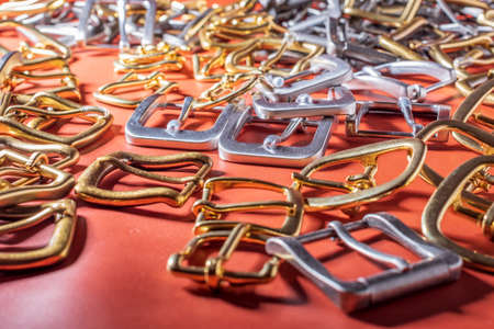 A lot of metal buckles for belts on red genuine full grain leather. Leather workshop. Stockfoto