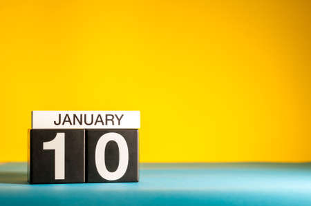 January 10th. Day 10 of january month, calendar on yellow background. Winter time. Empty space for text