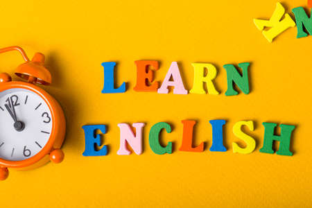 Word LEARN ENGLISH made with wooden letters on orange desk litle clock. Concept of English language courses.