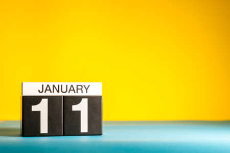 January 11th. Day 11 of january month, calendar on yellow background. Winter time. Empty space for text