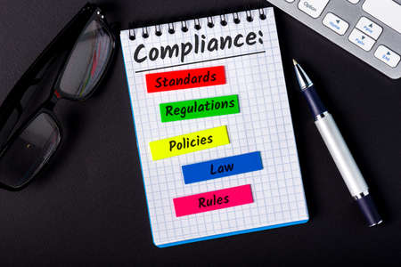 Compliance concept, components of compliance policies at notepad at office workplace.