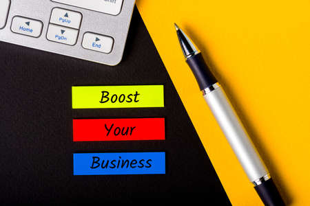 BOOST YOUR BUSINESS Motivational phrase on the desktop. Business Growth and Digital