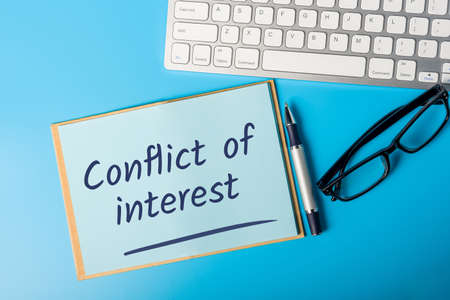 Conflict of Interest written in notebook of compliance officer workplace Stock Photo
