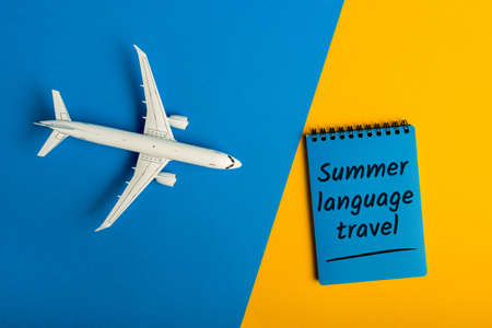 Summer language travel - message on color background with airplane toy. Learning English language and studying abroad
