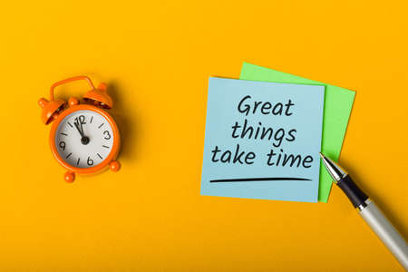 Great things take time - written in note on desk with little clock.