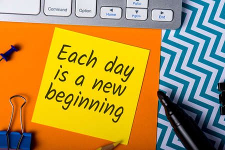 Each day is a new beggining - motivational note on office background