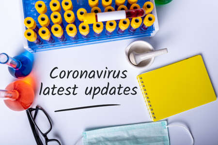 Research lab background with note COVID-19 latest UPDATES. Coronavirus concept and quarantine