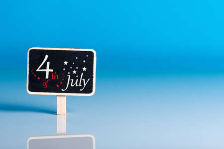 Independence Day Celebration. July 4th. Image of july 4 tag calendar at blue desk background with copy space. Summer day Standard-Bild