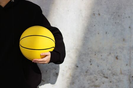 Young basketball player girl dressed in a black hoodie taking a yellow basketball. Sport concept. Foto de archivo - 135421422