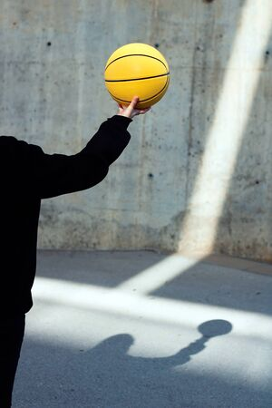Young basketball player girl dressed in a black hoodie taking a yellow basketball. Sport concept. Foto de archivo - 135421433