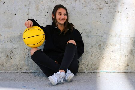 Young basketball player girl dressed in a black sweatshirt smiling and sitting in an urban court picking up a yellow basketball. Sport concept. Foto de archivo - 135421486