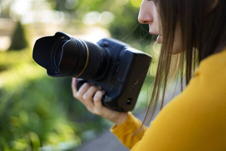 Videograph woman holding her reflex camera in the woods. Vlogger Womens Concept. Stock Photo