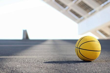 Yellow basketball on an asphalt ground. Basketball concept. Foto de archivo - 135421561