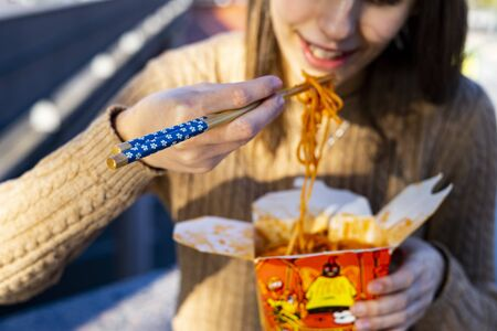Girl eating Chinese noodles with some blue chopsticks. Concept of chopsticks.