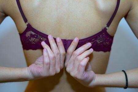 Woman putting on a fuchsia bra. Bra and brassiere concept.