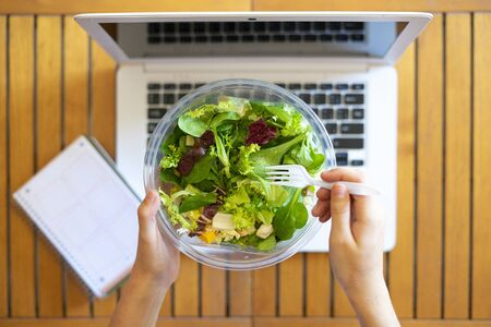 Office worker eating a takeaway salad at work. Concept of healthy eating at work. Top view.