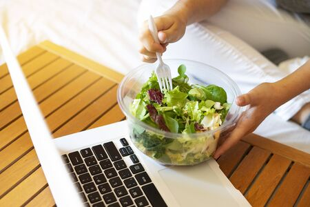 Office worker eating a takeaway salad at work. Concept of healthy eating at work. Diet at work.