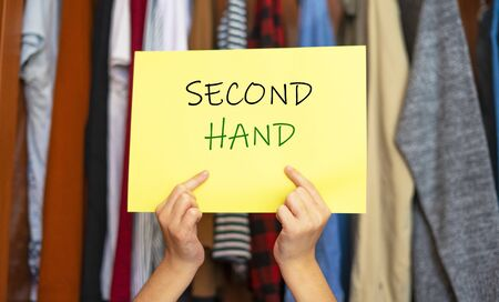 Hands picking up a sign that says Second Hand. Second hand clothing concept. Buy pre-owned clothing.
