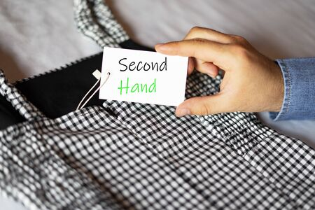 Man taking a label that says Second Hand. Clothing label. Second hand clothing concept. Stock fotó