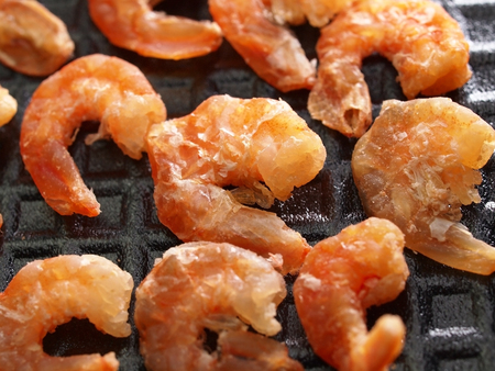 Dry small shrimps on black foam plate photo