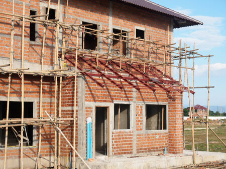 Under-construction house building with bamboo frame support photo