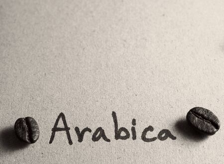Roasted arabica coffee beans on paper texture with text, retro monotone color background Stock Photo